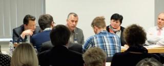 Mitglieder des Forum Silberhöhe sitzen an einem langen Tisch vor dem Audiotorium während einer Sitzung.